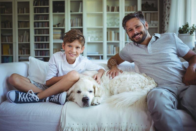 Padre e hijo que se sientan en el sofá con el perro casero en sala de estar foto de archivo libre de regalías