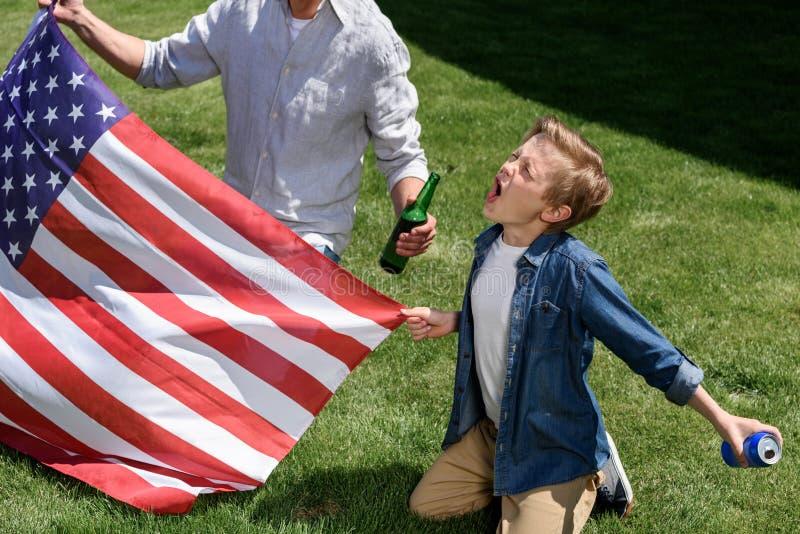 Padre e hijo que sientan en hierba con nosotros la bandera, muchacho que grita y que sostiene la poder de soda foto de archivo libre de regalías