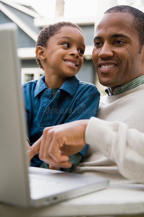 Padre e hijo que usa la computadora portátil imagen de archivo