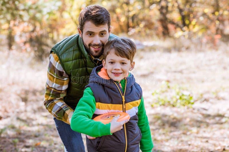 Padre e hijo sonrientes que juegan con el disco volador fotografía de archivo libre de regalías