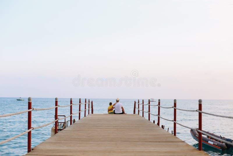 Padre e hijo y mirada del horizonte de mar y del cielo azul Vacaciones de familia en el mar Fondo de las vacaciones del mar del t imagen de archivo