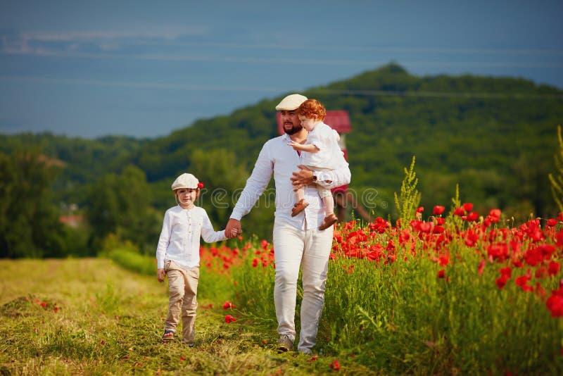 Padre e hijos que caminan a través del campo de flor de la amapola en el día de verano imágenes de archivo libres de regalías
