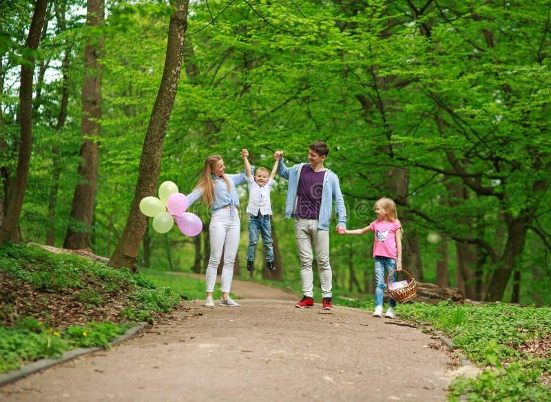 Padre e madre della famiglia con due bambini che camminano nel parco verde della citt? di estate sul picnic, sui genitori felici  immagine stock