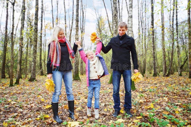 Padre e madre felice con la figlia dell'ascensore delle foglie immagini stock libere da diritti