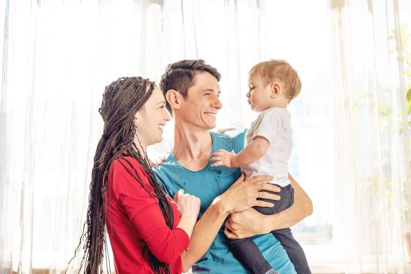 Padre e madre felice dei genitori che gioca con il figlio del bambino al sul fondo della finestra Giovane famiglia allegra e mode fotografie stock