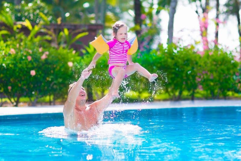 Padre e neonata che giocano in una piscina immagine stock