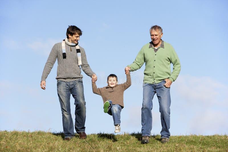 Padre e nonno che oscillano giovane ragazzo immagine stock