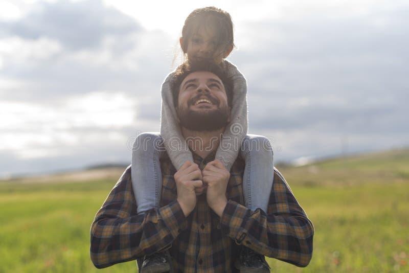 Padre e piccola figlia che giocano all'aperto nel giorno di primavera fotografia stock