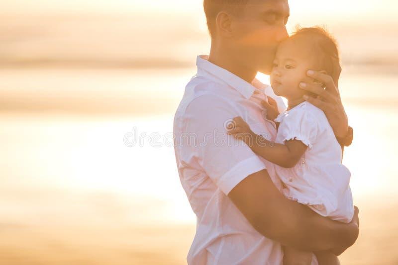 Padre e piccola figlia del bambino sulla spiaggia al tramonto fotografia stock