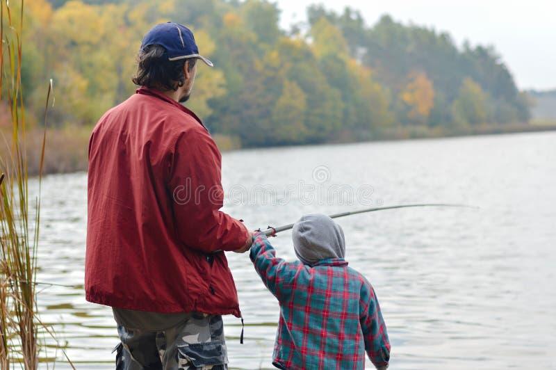 Padre e piccolo figlio che pescano insieme sul backgound di giorno di autunno fotografia stock libera da diritti