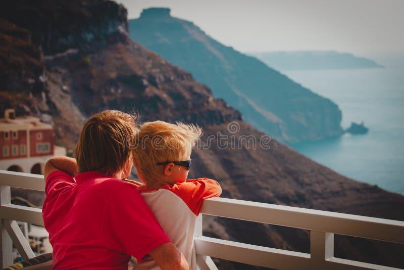 Padre e poco figlio che esaminano caldera in Santorini, Grecia fotografia stock libera da diritti