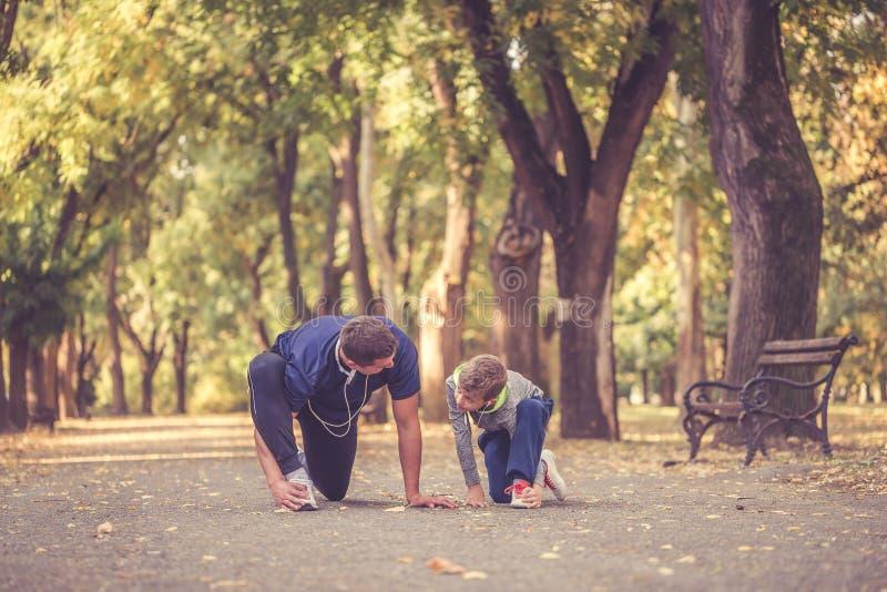 Padre e poco figlio che si esercitano insieme nel parco fotografia stock