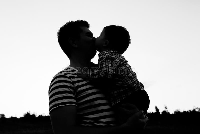 Padre ed il suo piccolo figlio che giocano all'aperto Il ragazzo bacia il suo papà fotografia stock libera da diritti