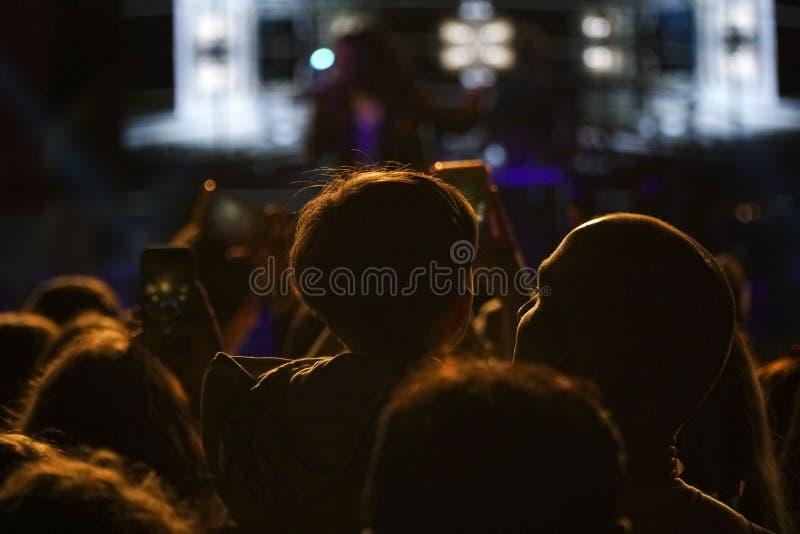 Padre ed il suo piccolo figlio in un concerto ad all'aperto fotografia stock