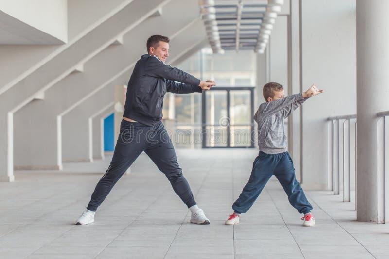 Padre ed suo figlio o ragazzino che allungano insieme armi fotografie stock