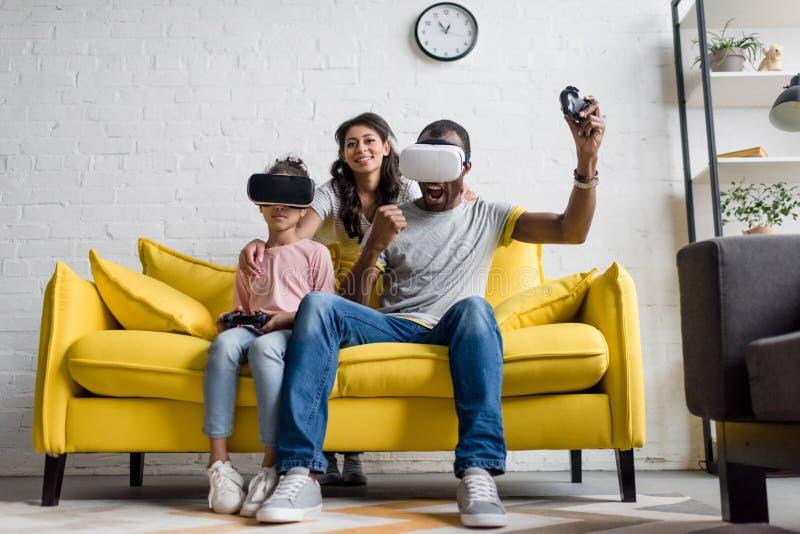 padre emozionante e figlia che giocano i video giochi mentre madre che si siede dietro fotografia stock