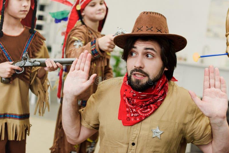padre en sombrero y pañuelo y pequeños hijos en trajes indígenas con los juguetes que juegan junto fotos de archivo