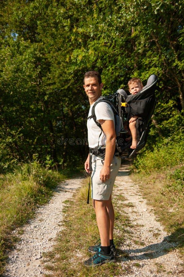 Padre en un paseo con el kik en mochila del portador del niño imagen de archivo libre de regalías