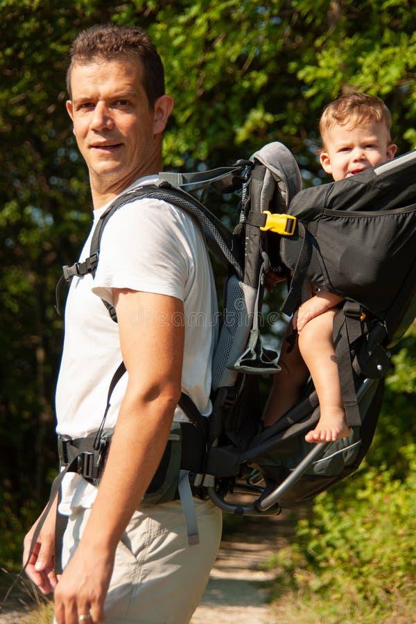 Padre en un paseo con el kik en mochila del portador del ni?o fotografía de archivo libre de regalías