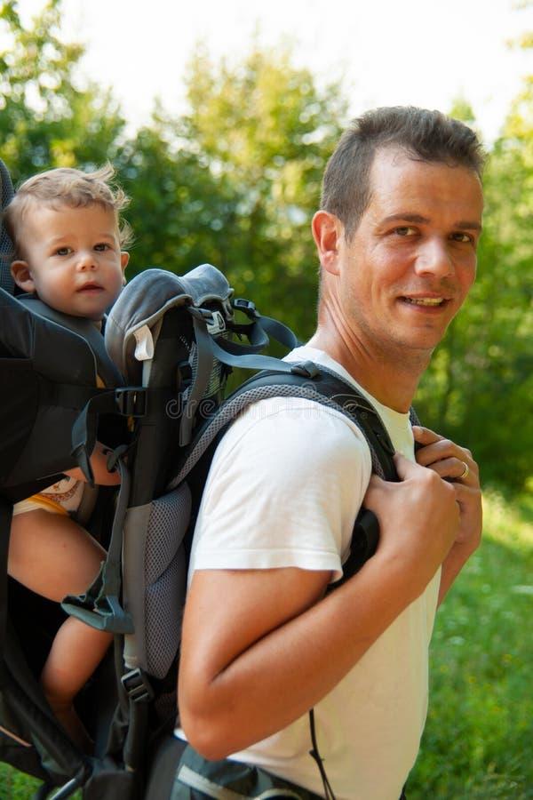 Padre en un paseo con el kik en mochila del portador del ni?o fotos de archivo libres de regalías