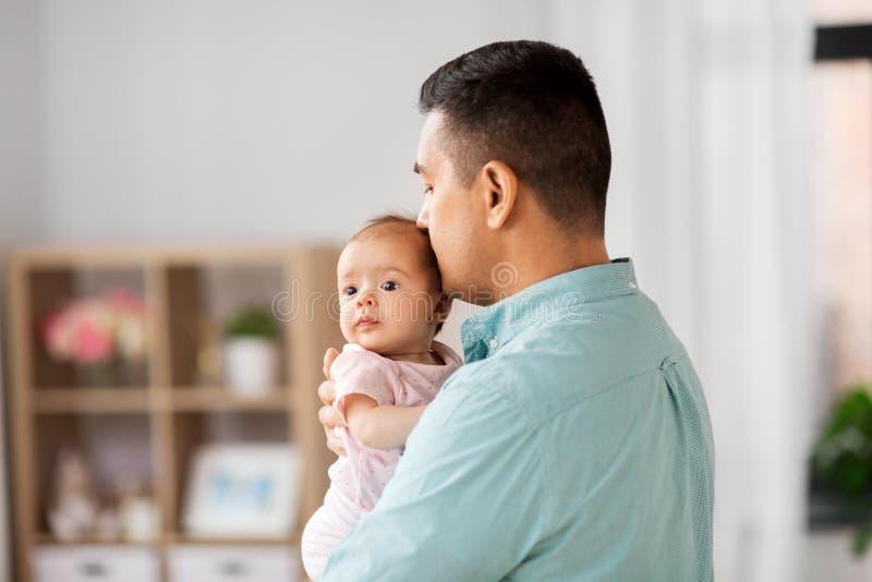 Padre envejecido medio con la hija del bebé en casa imagenes de archivo