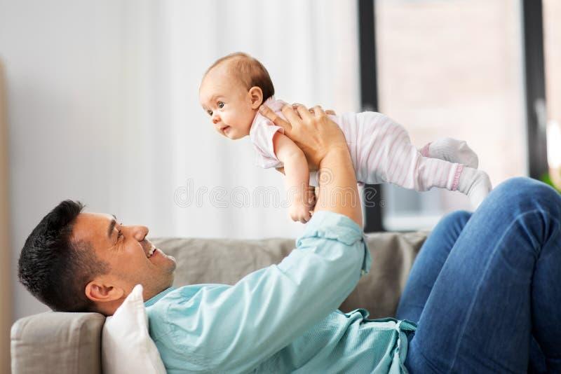 Padre envejecido medio feliz con el bebé en casa imagen de archivo libre de regalías