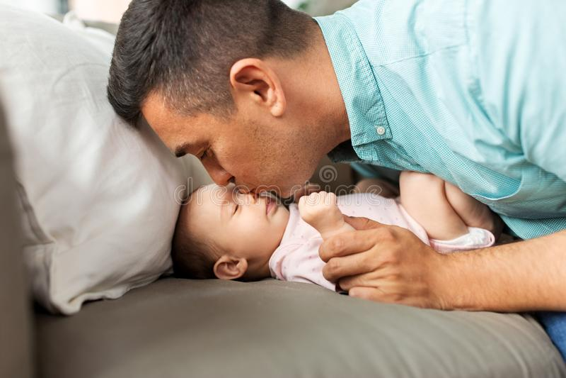 Padre envejecido medio que besa a la hija del bebé en casa foto de archivo