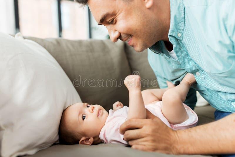 Padre envejecido medio que juega con el bebé en casa imagen de archivo