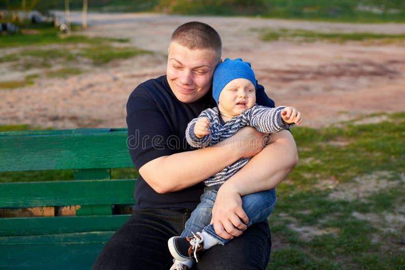 Padre felice che abbraccia suo figlio arrabbiato su un banco nel parco immagini stock libere da diritti