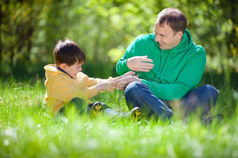 Padre felice che gioca con il suo piccolo figlio all'aperto immagine stock