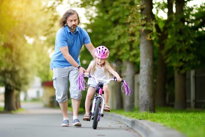 Padre felice che insegna alla sua piccola figlia a guidare una bicicletta Bambino che impara guidare una bici fotografie stock libere da diritti