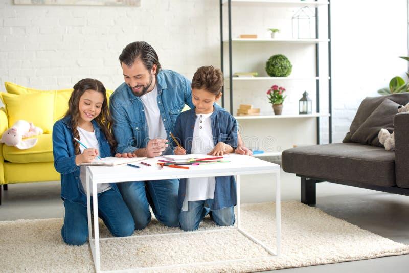 padre felice con due bambini che si inginocchiano sul tappeto e che disegnano con le matite colorate fotografie stock libere da diritti