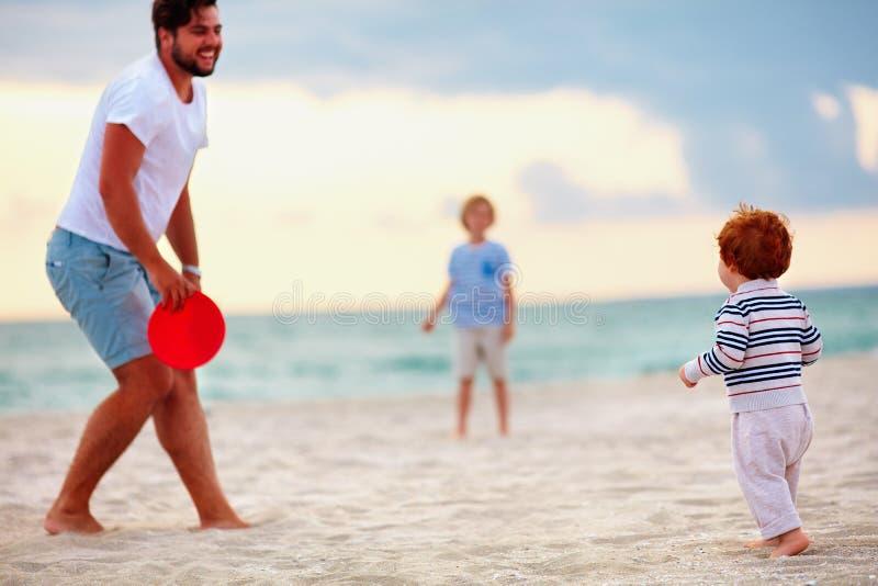 Padre felice con i bambini, famiglia che gioca golf del disco di volo sulla spiaggia di sera fotografia stock