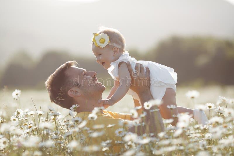 Padre felice con la piccola figlia che gioca di estate in un campo delle margherite bianche immagini stock libere da diritti