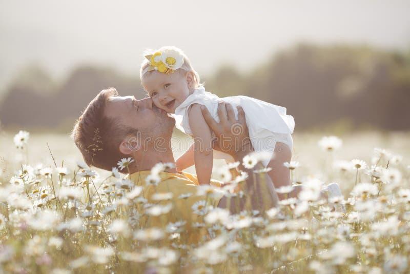Padre felice con la piccola figlia che gioca di estate in un campo delle margherite bianche fotografia stock