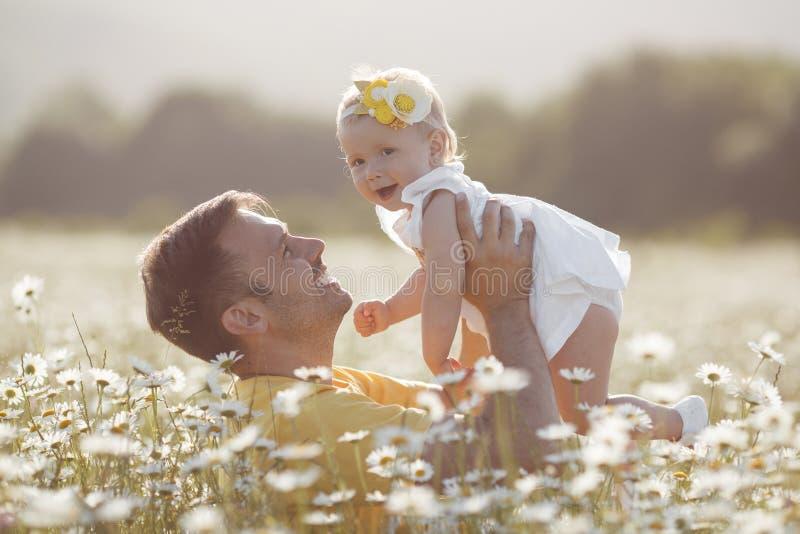 Padre felice con la piccola figlia che gioca di estate in un campo delle margherite bianche fotografie stock
