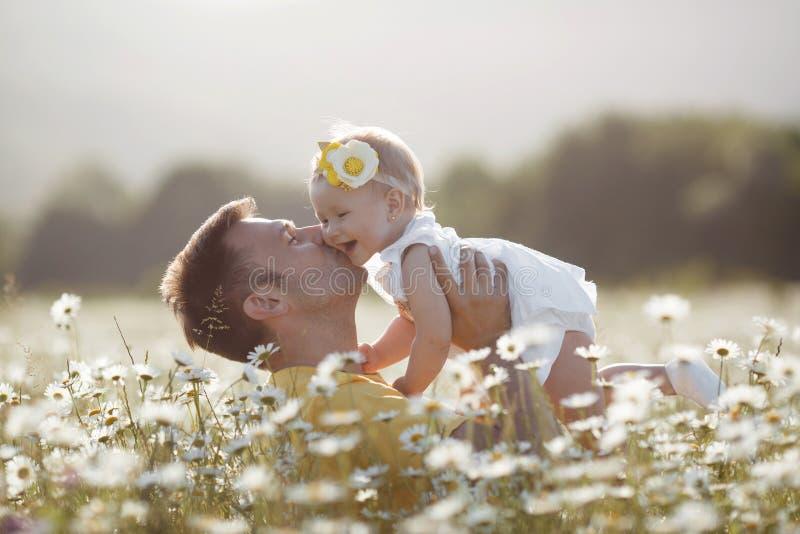 Padre felice con la piccola figlia che gioca di estate in un campo delle margherite bianche immagine stock libera da diritti