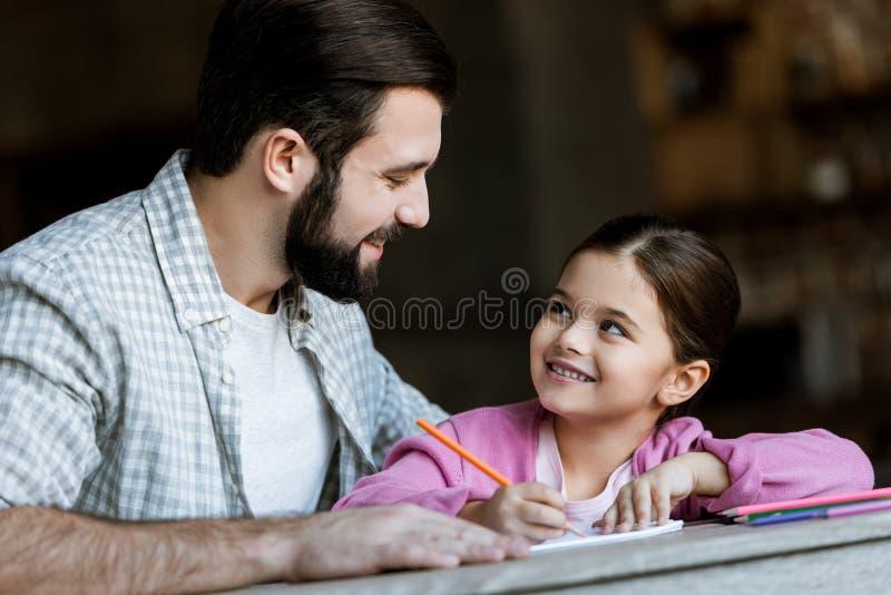 padre felice con la piccola figlia che si siede alla tavola e che assorbe album per ritagli immagine stock libera da diritti