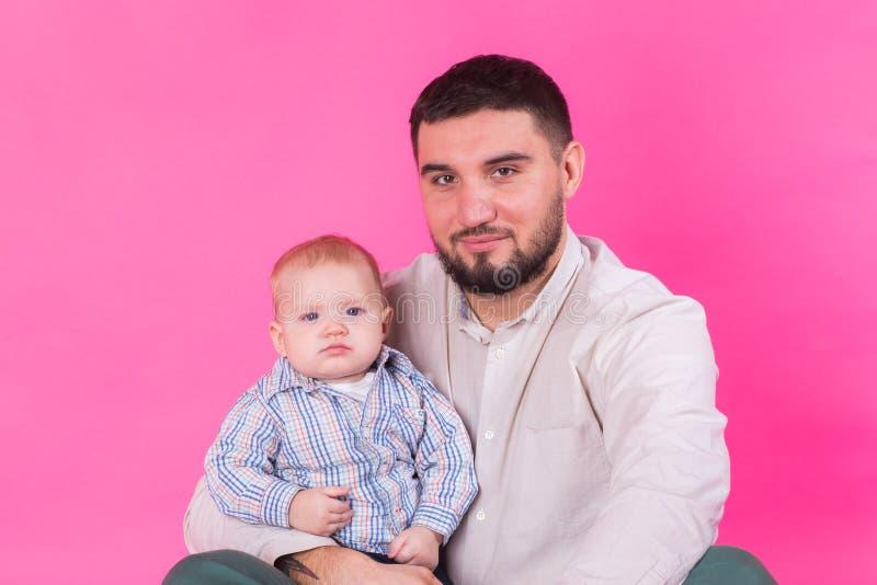 Padre felice con un figlio del bambino isolato su un fondo rosa fotografia stock libera da diritti