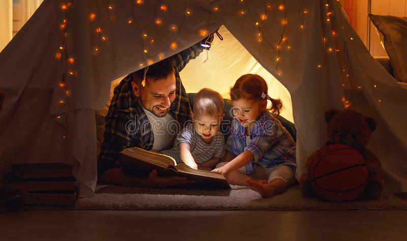 Padre felice e bambini della famiglia che leggono un libro in tenda al hom immagini stock
