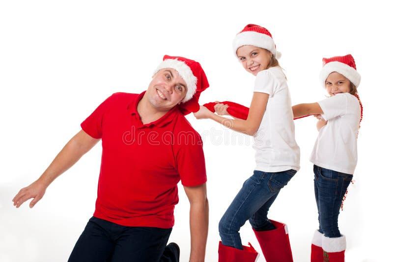 Padre felice e due figlie nella risata dei cappelli di Santa fotografie stock