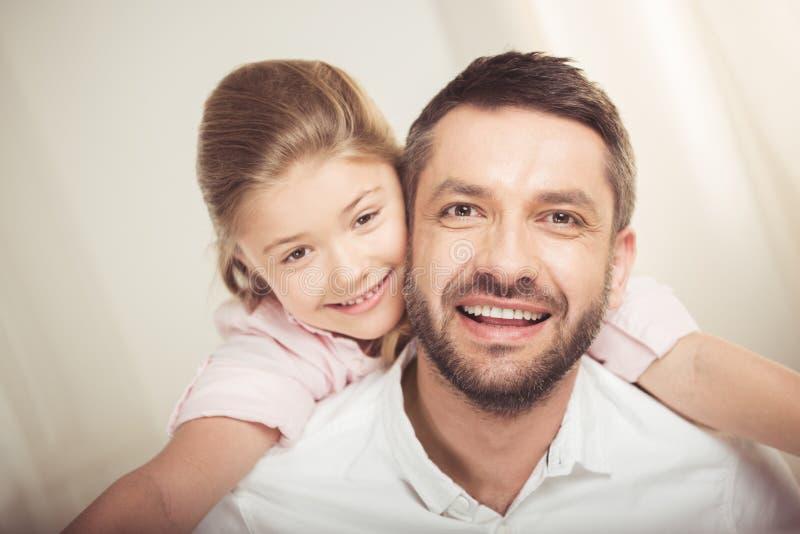 Padre felice e figlia che abbracciano e che sorridono alla macchina fotografica fotografia stock libera da diritti