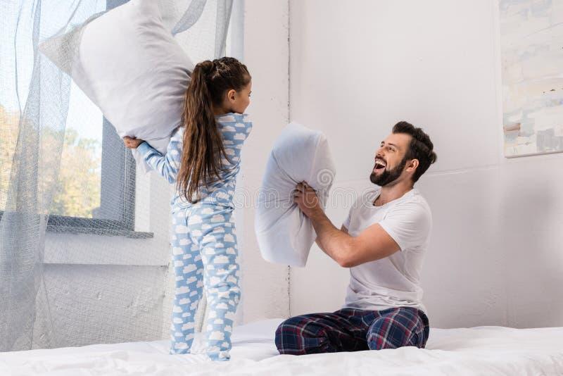 padre felice e figlia che giocano lotta di cuscino a letto immagine stock libera da diritti