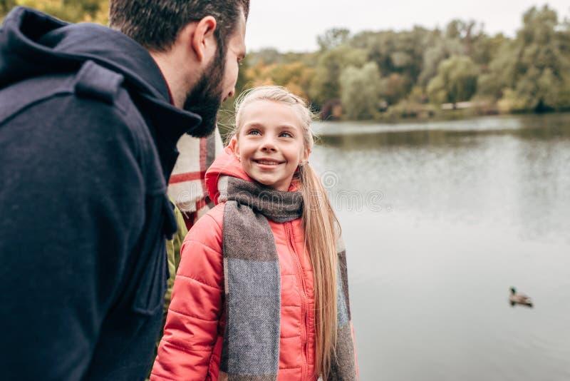 padre felice e figlia che si sorridono mentre stando vicino al lago immagine stock libera da diritti