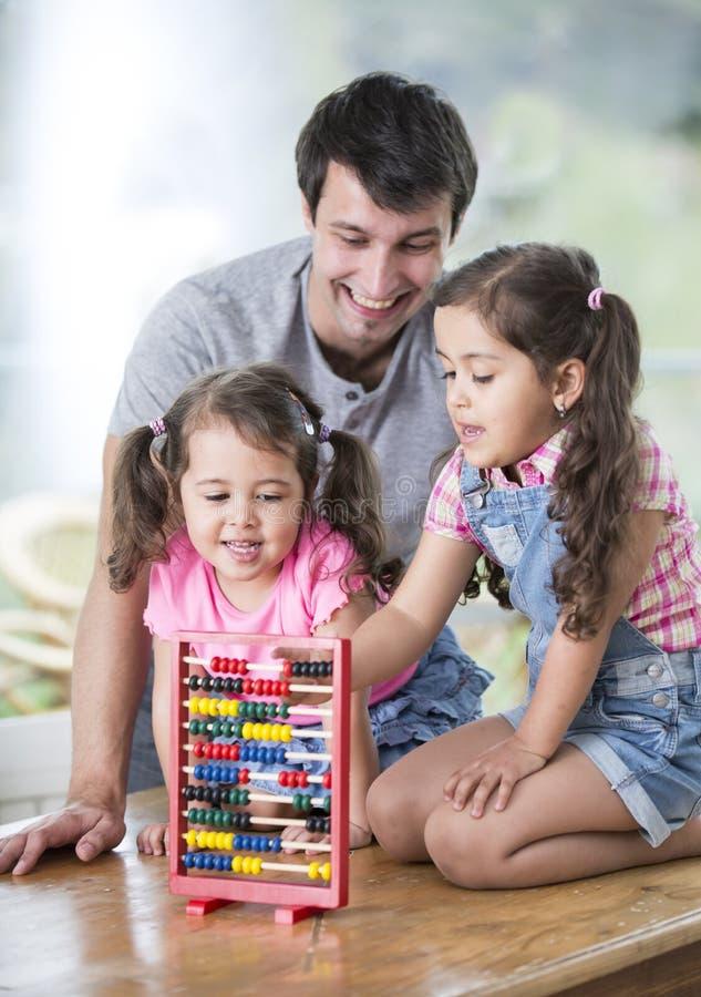 Padre felice e figlie che giocano con l'abaco in casa fotografie stock