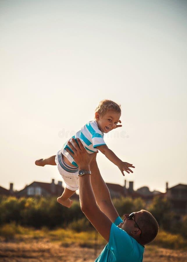 Padre felice e figlio che giocano insieme alla spiaggia Padre che getta suo figlio nell'aria fotografia stock