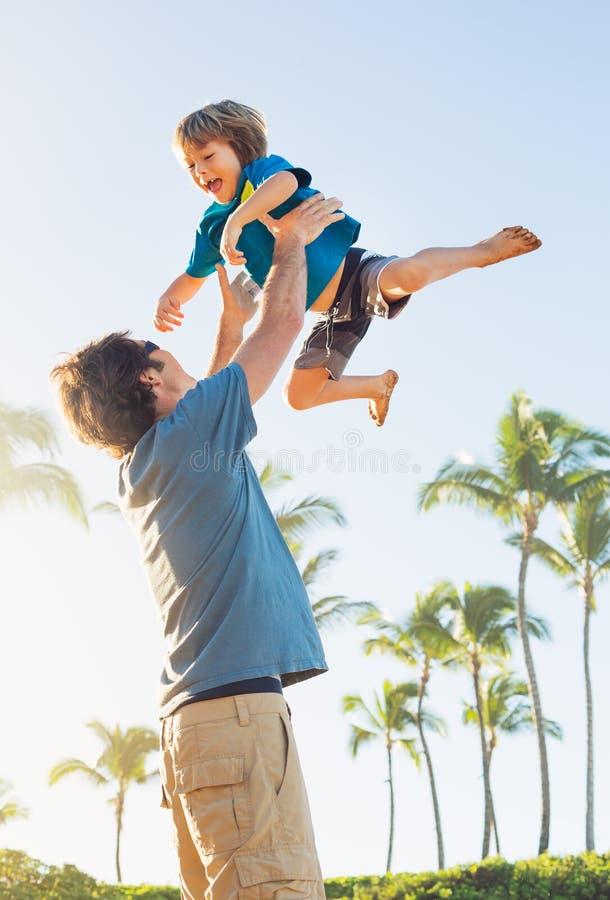 Padre felice e figlio che giocano sulla spiaggia tropicale, f felice spensierata immagini stock
