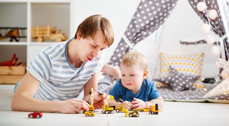 Padre felice e figlio della famiglia che giocano in automobile del giocattolo in stanza dei giochi immagini stock
