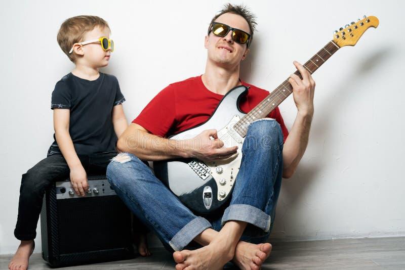 Padre felice e piccolo figlio che giocano insieme chitarra immagini stock