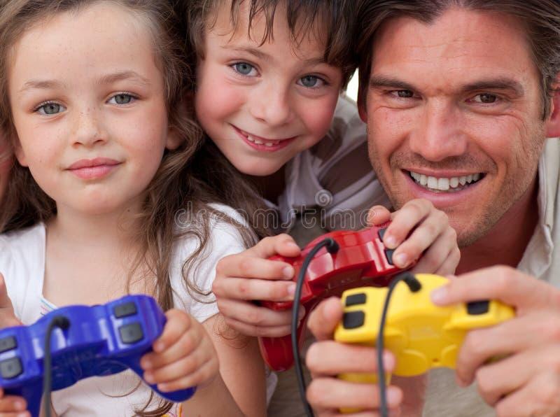 Padre felice e suoi i bambini che giocano i video giochi fotografie stock